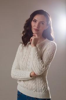 Женщина, поднимая левую руку и касаясь пальцем подбородка, о чем-то думает. концепция моды