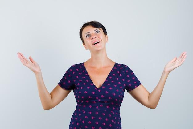 腕を上げて、ドレスを着て見上げて、幸せそうに見える女性