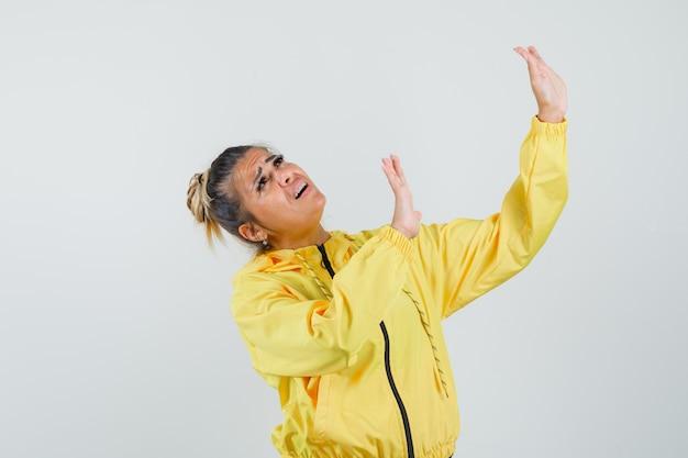 Donna che alza le mani per difendersi in tuta sportiva e sembra spaventata, vista frontale.