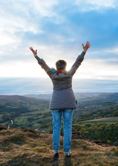 Woman raising hands high and standing on top of mountain