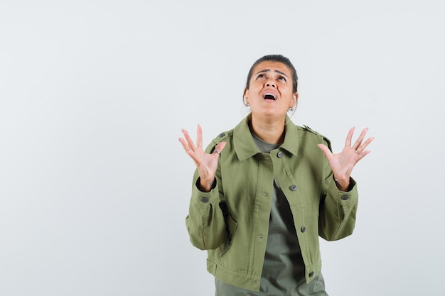 Woman raising hands, looking up in jacket, t-shirt and looking helpless.