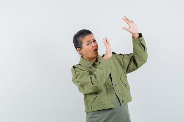 Woman raising hands in protective manner in jacket, t-shirt and looking scared.
