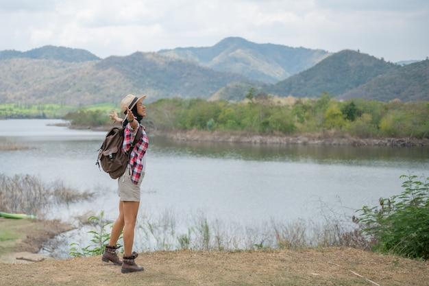 湖のほとりで手を上げる女性/前のアジアの女性ハイカーは幸せな笑顔、森の中でハイキングする女性、暖かい夏の日。