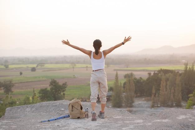 Женщина поднимает руки вверх на вершине горы во время пеших прогулок и столбов, стоящих на скалистом горном хребте, глядя на долины.