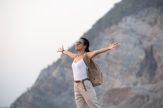 Woman raising hands up on the top of a mountain while hiking and poles standing on a rocky mountain ridge looking out valleys and peak.