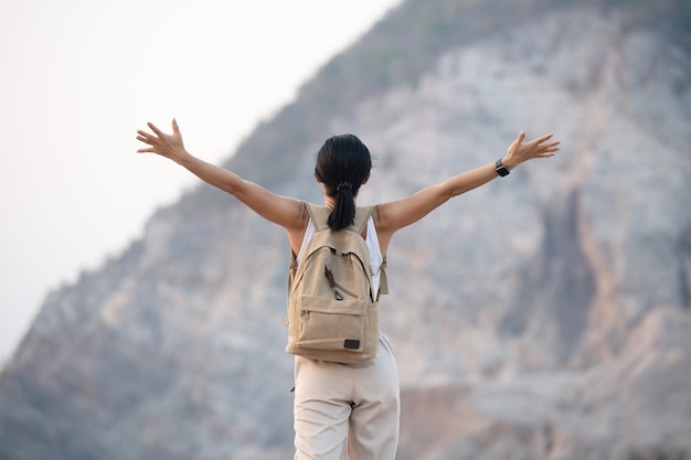 Woman raising hands up on the top of a mountain while hiking and poles standing on a rocky mountain ridge looking out valleys and peaks.