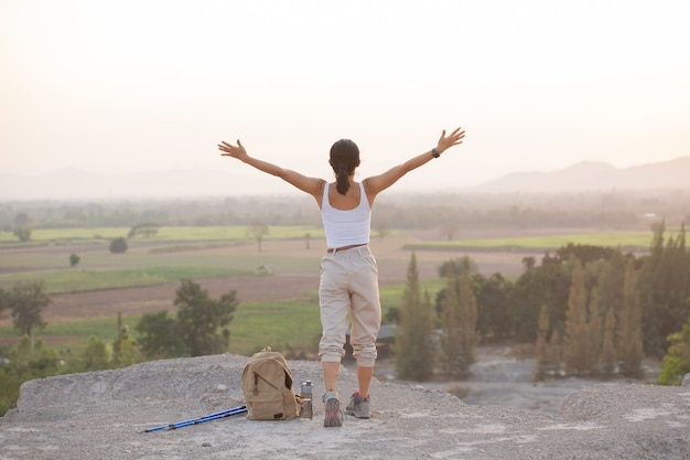 Woman raising hands up on the top of a mountain while hiking and poles standing on a rocky mountain ridge looking out valleys.