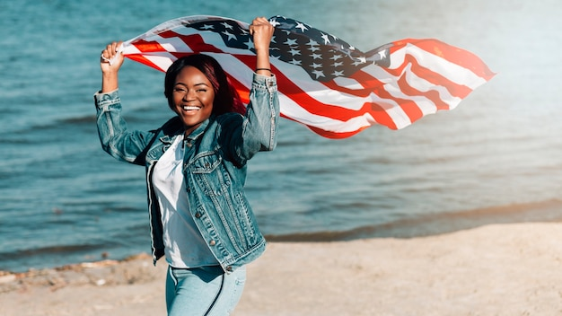 Woman raising hands with american flag on seashore