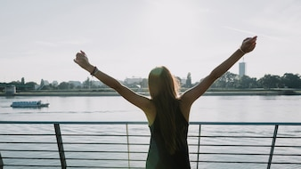 Woman raising her arms in front of river at outdoors