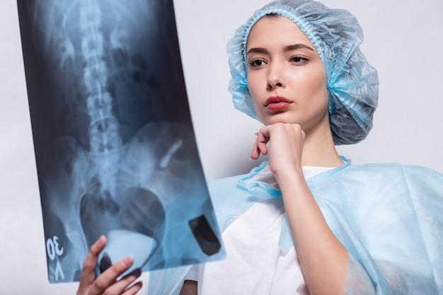 그녀의 손을 들고 엑스레이 사진을 들고 여자 의사 의학, 의사는 엑스레이 사진을 검사합니다. 그녀의 손으로 보호 마스크를 쓰고 폐의 스냅샷을 들고 있는 여자.