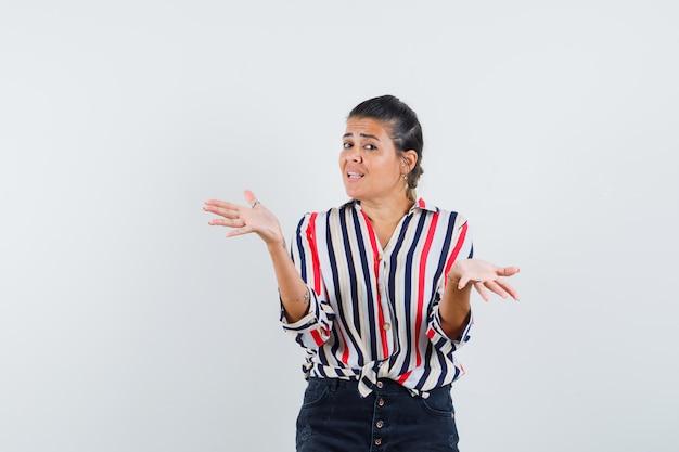 Женщина в рубашке, юбке поднимает раздвинутые ладони и выглядит смущенной