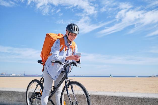 彼女のスマートフォンを見ているビーチで自転車でラップする女性