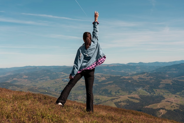 Woman reached the top of mountain and celebrating