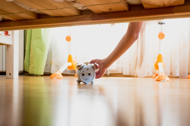 Woman reaching under the bed and pressing snooze button on alarm clock