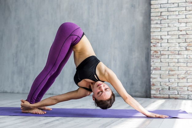 Woman reaching her leg while standing in a downward-facing dog pose