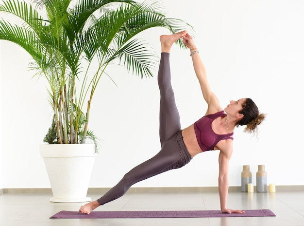 Woman reaching her toes in side plank