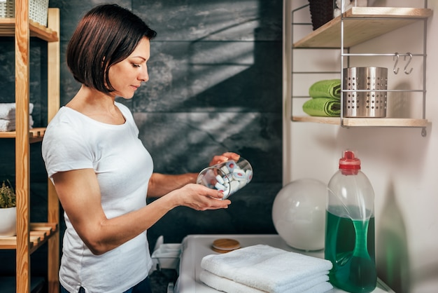 Woman reaching for washing machine cleaner tablet