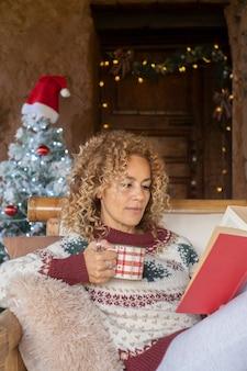 女性はバックグラウンドでクリスマスの装飾と本を読む