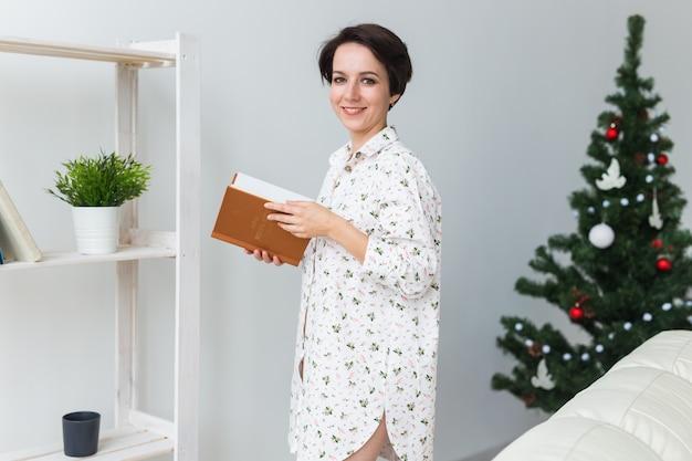 女性はクリスマスツリーのあるリビングルームで本を読む