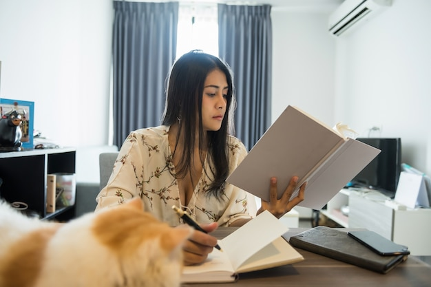Woman read book and write paper in room