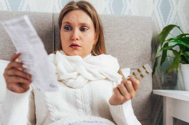 Woman read medicine leaflet before taking pills lying in bed