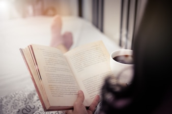 Woman reading a book and holding cup of coffee in the morning.