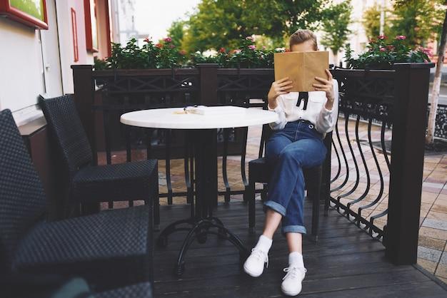 Женщина читает книгу за столом в блокноте кафе студентка джинсы кроссовки рубашка