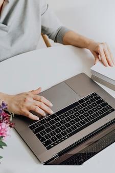 그녀의 노트북으로 책을 읽는 여자