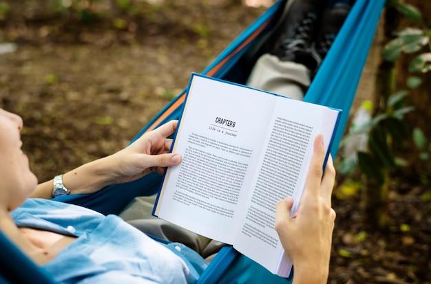 ハンモックで本を読んでいる女性