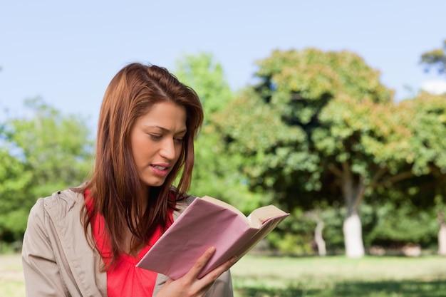 햇볕이 잘 드는 목초지 지역에서 책을 읽는 여자