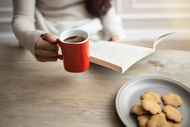 Женщина читает книгу по утрам и пьет кофе