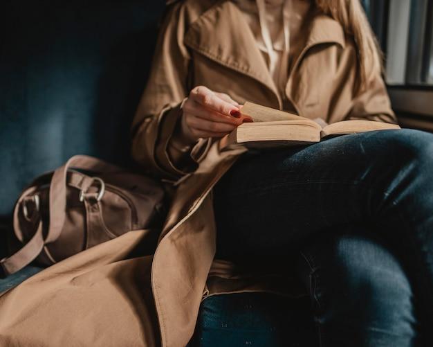 電車の中で本を読んでいる女性