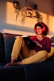 Женщина читает книгу на диване во время карантина из-за коронавируса - концепция оставайся дома
