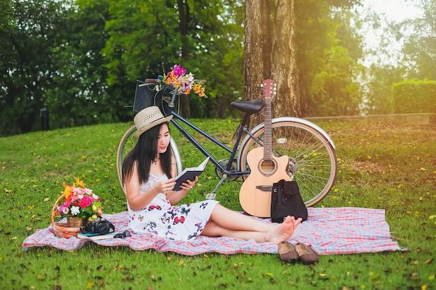 時間のリラックスの本を読んでいる女性。アジアの女性は休暇の公共公園でピクニックを持っている