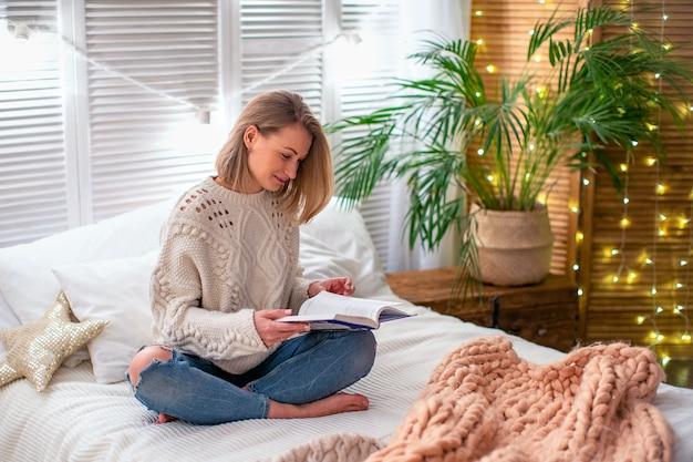 Женщина читает книгу на кровати. девушка встречает рождество