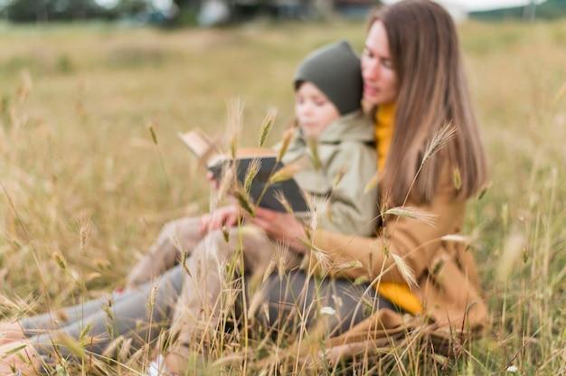 屋外で息子に本を読む女