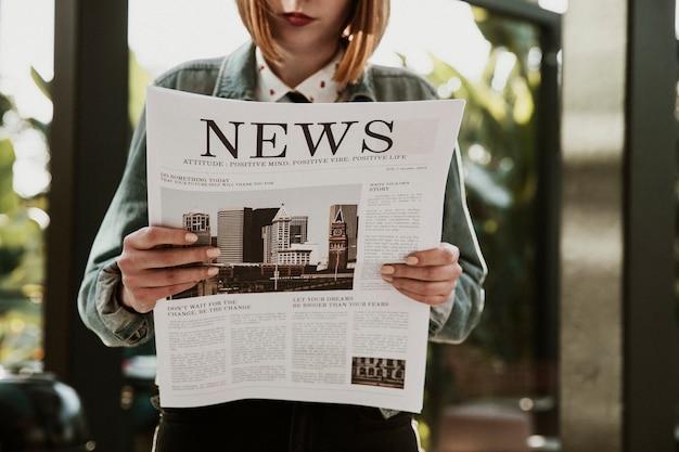 カフェで新聞を読んでいる女性
