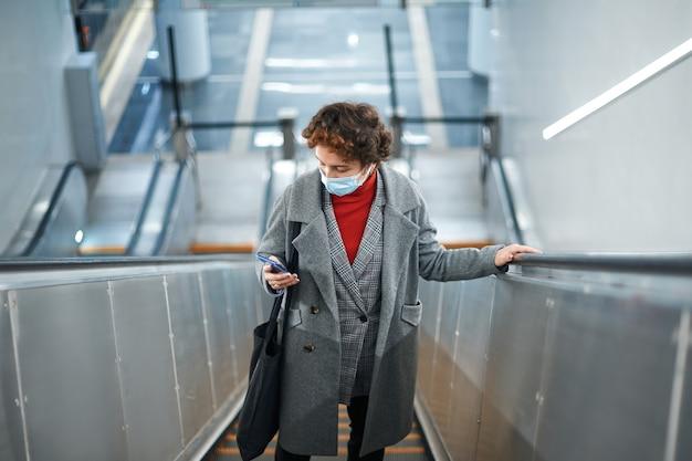 エスカレーターの階段に立ってメッセージを読む女性