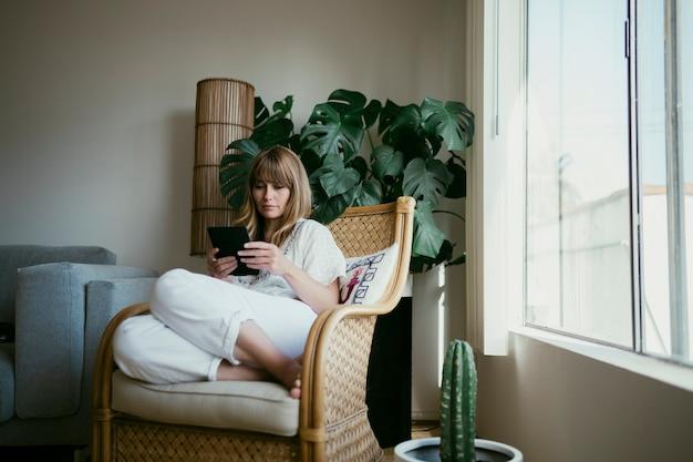 コロナウイルス検疫中にデジタルタブレットで電子書籍を読んでいる女性