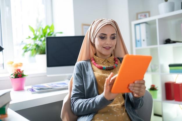 読書する女性。ヒジャーブを身に着けている魅力的なイスラム教徒の女性が喜びを感じて電子書籍を読んでいます