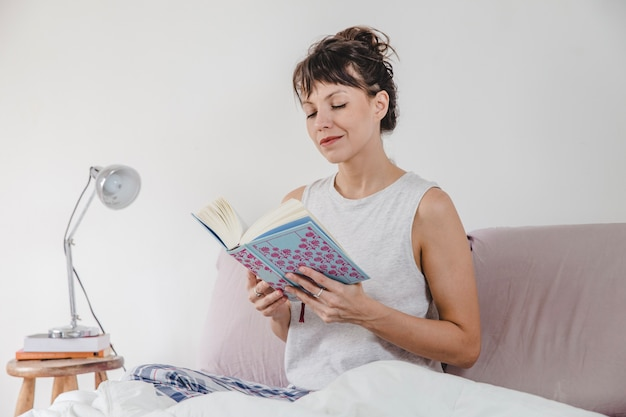 Woman reading in bed in the morning