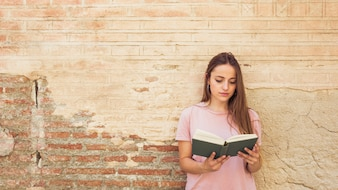 Woman reading book against weathered wall