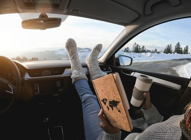 겨울날 케어 안에서 책을 읽고 커피를 마시는 여성 - 따뜻한 양말에 초점