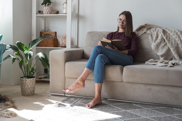 本を読んで、自宅のソファに座ってリラックスする女性