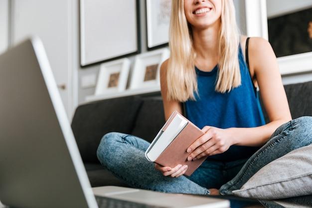 本を読んで、自宅のソファーでノートパソコンを使用しての女性
