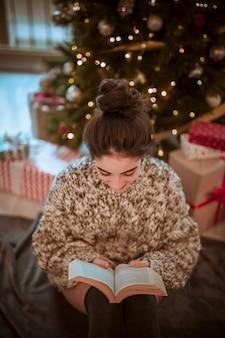 Woman reading book at Christmas tree