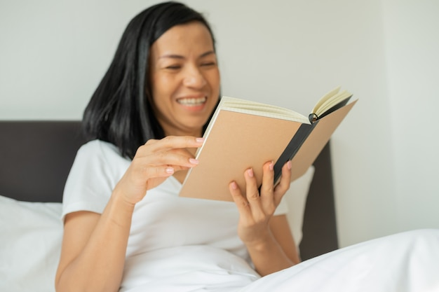 寝室で自宅で本を読んでいる女性。