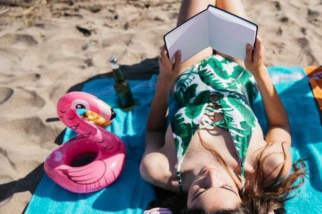 Женщина читает книгу на пляже