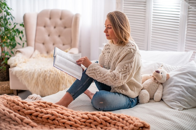 Woman reading a book on the bed