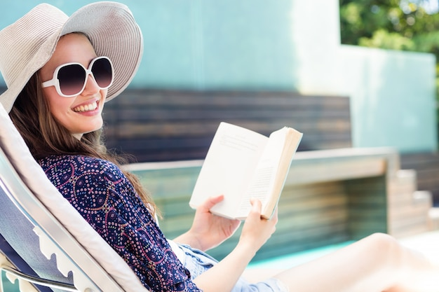 Woman reading a book by swimming pool